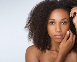 Close up portrait of an african american female fashion model posing with hands by face